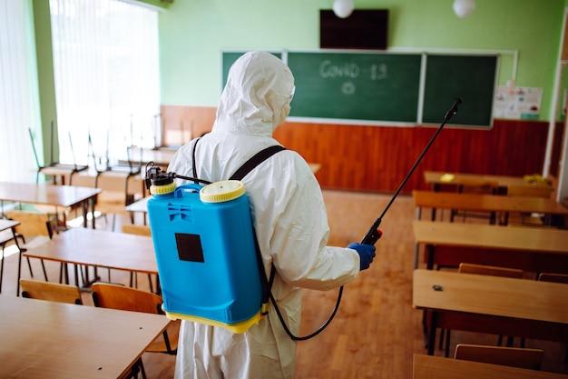 Widok z tyłu profesjonalnego pracownika sanitarnego dezynfekującego salę przed rozpoczęciem roku akademickiego. mężczyzna w kombinezonie ochronnym oczyszcza audytorium z koronawirusa covid-19. opieka zdrowotna.