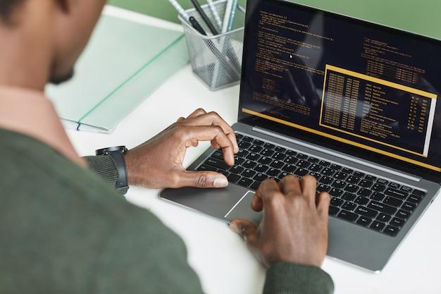 Widok z tyłu programisty piszącego na laptopie, rozwijającego oprogramowanie, które pracuje w miejscu pracy w biurze