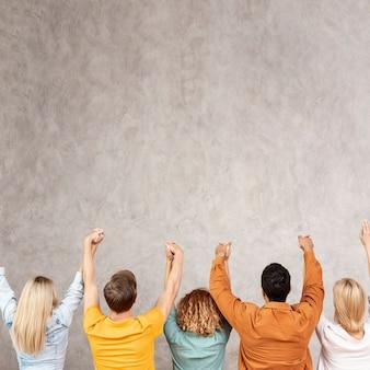 Widok z tyłu przyjaciele trzymając ręce do góry