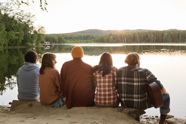 Widok z tyłu przyjaciół grających na gitarze, siedzących na brzegu i podziwiających piękne jezioro na świeżym powietrzu
