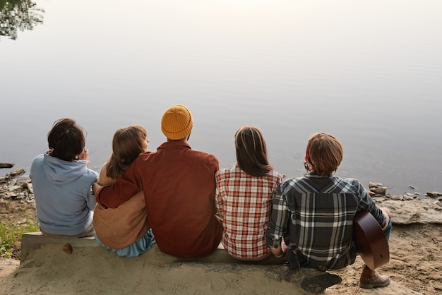 Widok z tyłu przyjaciół siedzących na zewnątrz i cieszących się pięknym krajobrazem jeziora