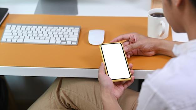 Widok z tyłu przypadkowy mężczyzna siedzący przy biurku i przy użyciu inteligentnego telefonu.