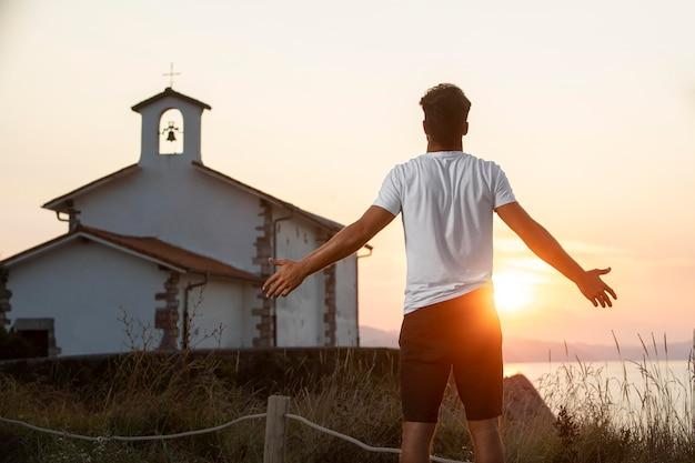 Widok z tyłu przystojny mężczyzna podróżnik cieszący się zachodem słońca