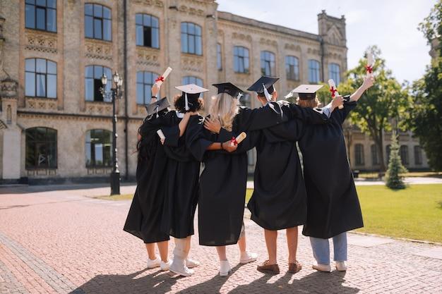 Widok z tyłu przytulających się absolwentów spoglądających na swój uniwersytet po raz ostatni