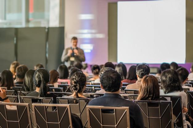Widok z tyłu publiczności w sali konferencyjnej lub na spotkaniu seminaryjnym, które mają głośnik
