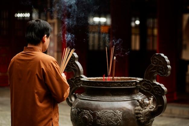 Widok z tyłu religijnego człowieka w świątyni z płonącym kadzidłem