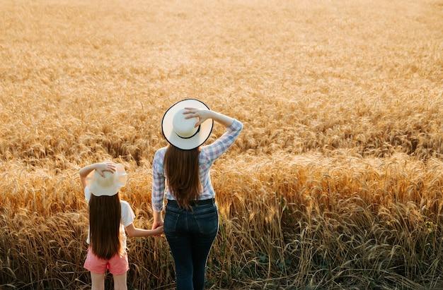 Widok z tyłu rodzinnego rolnika i dziecka w kapeluszu na złotym polu pszenicy o zachodzie słońca