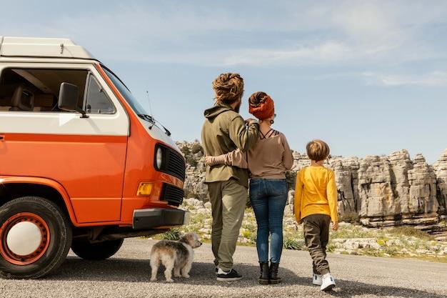 Widok z tyłu rodziny z psem w podróży