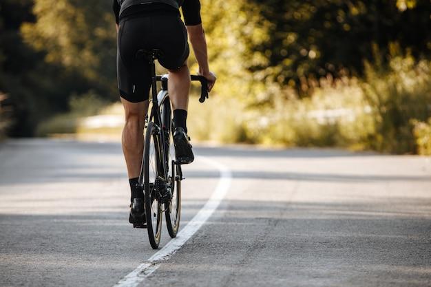 Widok z tyłu rowerzysty w odzieży sportowej jeżdżącej na profesjonalnym rowerze na utwardzonej drodze z rozmyciem tła zielonych roślin.