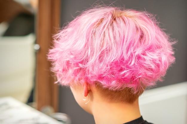 Widok z tyłu różowej fryzury młodej kobiety po farbowaniu włosów i podkreślaniu w salonie piękności