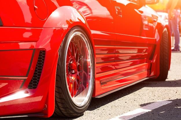 Widok z tyłu samochodu czerwony sportowy tuning koła, zbliżenie. dzień mody samochodu na drodze