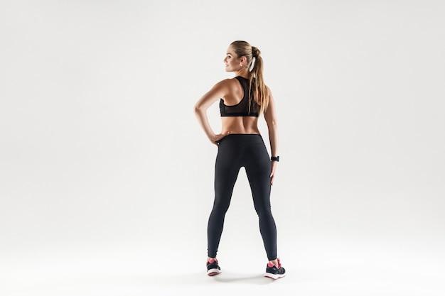 Widok z tyłu seksowna atrakcyjna i fitness dziewczyna. strzał studio, na białym tle na szarym tle