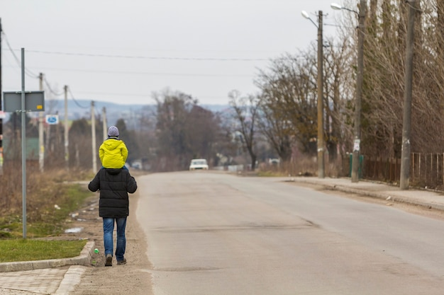 Widok z tyłu silnego wysportowanego mężczyzny ojca niosącego na ramionach małe dziecko w ciepłej, jasnej odzieży idącej wzdłuż podmiejskiej drogi w chłodne wiosenne mgliste poranki