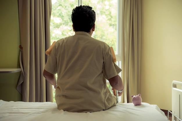 Widok z tyłu skarbonki z nogą mężczyzny używa kul do chodzenia po operacji rekonwalescencji urazów złamanych kości