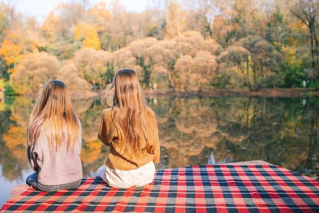Widok z tyłu słodkie dziewczyny, ciesząc się jesienny dzień nad jeziorem
