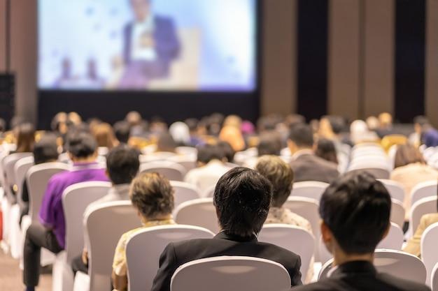 Widok z tyłu słuchania słuchaczy mówcy na scenie w sali konferencyjnej lub spotkaniu seminaryjnym, biznesie i edukacji na temat inwestycji