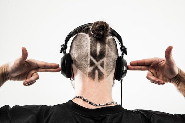 Widok z tyłu - słuchawki raperskie ze stylową fryzurą i tatuażem. zdjęcie na białej ścianie