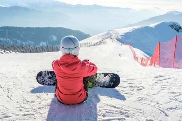 Widok z tyłu snowboardzista w odzieży sportowej ze sprzętem spoczywającym na szczycie stoku narciarskiego, ciesząc się widokiem