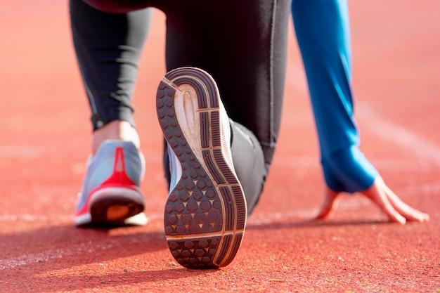 Widok z tyłu sportowca przygotowuje się do wyścigu na bieżni. skoncentruj się na bucie sportowca, który ma rozpocząć wyścig na stadionie.