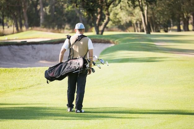 Widok z tyłu sportowca spaceru z jego torbę golfową
