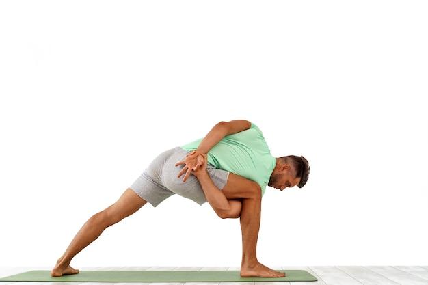 Widok z tyłu sportowego mężczyzny ćwiczącego jogę w zajęciach jogi, co rozciąga się z powrotem