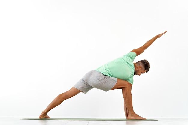 Widok z tyłu sportowego mężczyzny praktykującego jogę w zajęciach jogi, co rozciąga jogę zdrowego stylu życia
