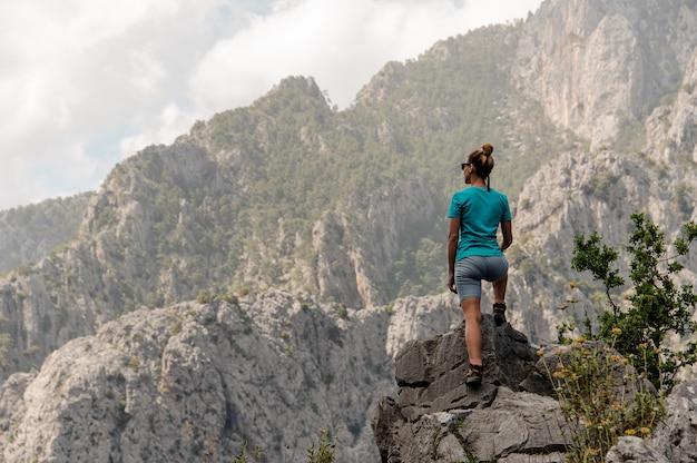 Widok z tyłu sportowy kobiety stojącej na skale na piękny krajobraz