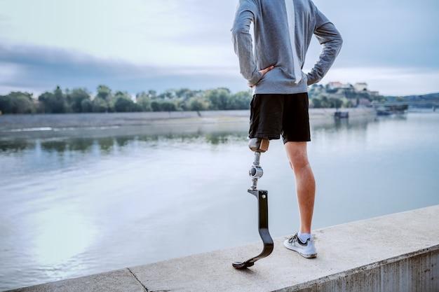 Widok z tyłu sprawnego zdrowego niepełnosprawnego mężczyzny rasy kaukaskiej w odzieży sportowej i ze sztuczną nogą, stojącego na nabrzeżu z rękami na biodrach.