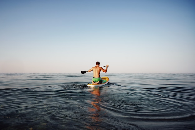 Widok z tyłu sprawny mężczyzna unoszący się na desce wiosłowej na morzu