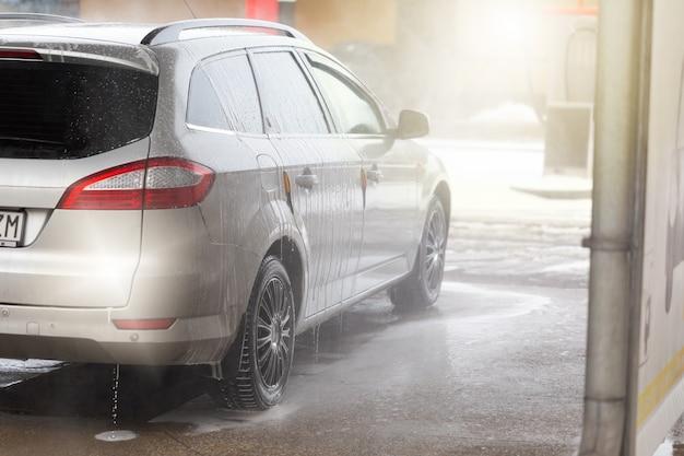 Widok z tyłu srebrnego samochodu mytego wodą i mydłem w myjni samochodowej