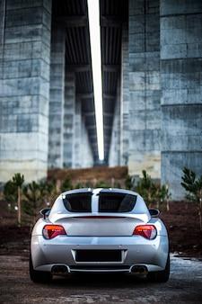 Widok z tyłu srebrnego sportowego sedana z czerwonymi światłami.