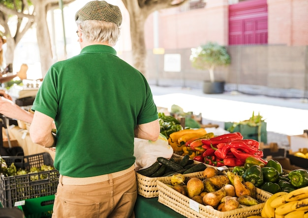Widok z tyłu starszy mężczyzna stojący na stoisku warzyw i owoców
