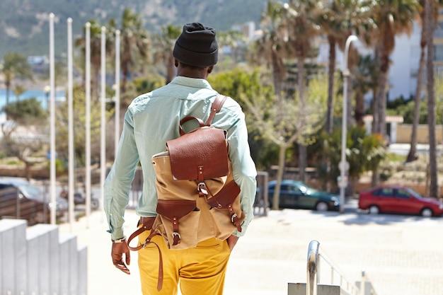 Widok z tyłu studentów płci męskiej spaceru na ulicy w słoneczny dzień