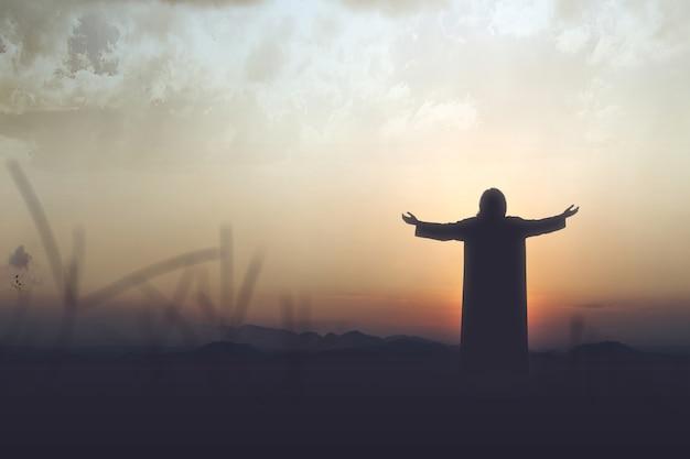 Widok z tyłu sylwetka jezusa chrystusa podniósł ręce i modlił się do boga z niebem o zachodzie słońca