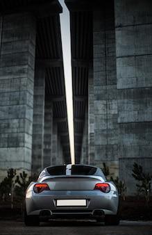 Widok z tyłu szary samochód stojący pod mostem.