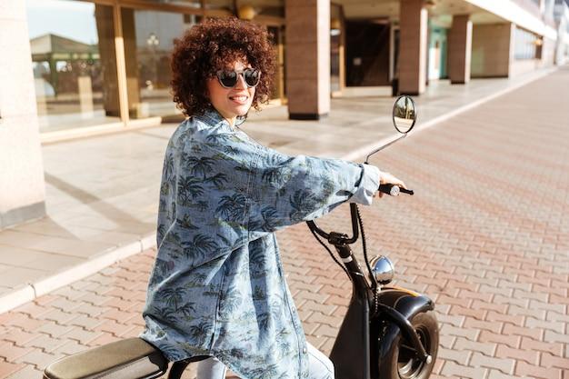 Widok z tyłu szczęśliwa kędzierzawa kobieta w sunglasess siedzi na nowożytnym motocyklu outdoors i patrzeje daleko od