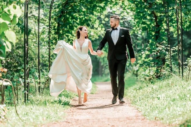 Widok z tyłu. szczęśliwa panna młoda i pan młody przechodzi pod łukiem ślubnym. wydarzenia i tradycje