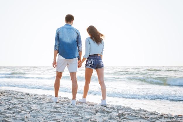 Widok z tyłu szczęśliwej młodej pary spacerującej i trzymającej się za ręce na plaży