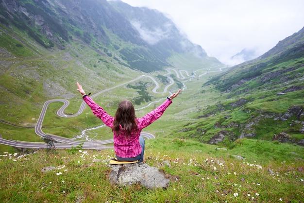 Widok z tyłu szczęśliwej podróżniczki cieszącej się wspaniałymi górskimi krajobrazami obserwującymi transfagarasan, siedzącą na wzgórzu w trawie z rozłożonymi rękami