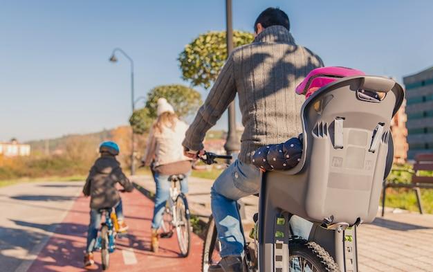 Widok z tyłu szczęśliwej rodziny z dziećmi jeżdżącymi na rowerach przez naturę w słoneczny zimowy dzień