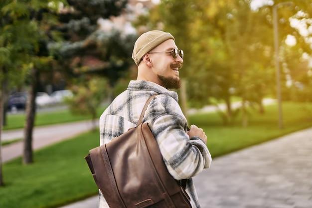 Widok z tyłu szczęśliwy hipster brodaty student pije kawę podczas spacerów w miejskim parku miejskim dzień odpoczynku