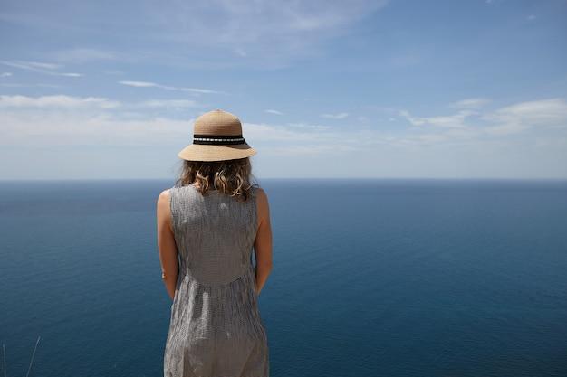 Widok z tyłu szczupła blondynka młoda kobieta ubrana w sukienkę i słomkowy kapelusz, ciesząc się słoneczną pogodą na zewnątrz, naprzeciwko rozległego błękitnego morza, patrząc w dal. ludzie, przyroda, pejzaż morski, lato i podróże