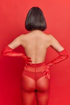 Widok z tyłu szczupłej, nierozpoznanej kobiety bez twarzy, która stoi tyłem do aparatu, ma na sobie majtki, czerwone rajstopy i długie rękawiczki na ramionach, pokazuje, że jej ciało seksualne ma ciemne, przystrzyżone włosy pozuje w pomieszczeniu