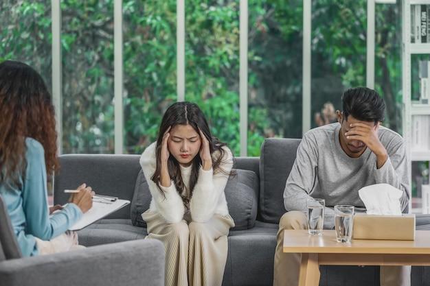 Widok z tyłu trenera słuchającego i patrzącego azjatyckich młodych kochanków to smutek z powodu ich problemu