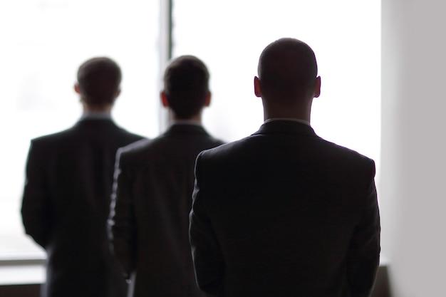 Widok z tyłu trzech biznesmenów, którzy wpatrują się w duże okno z widokiem na miasto.