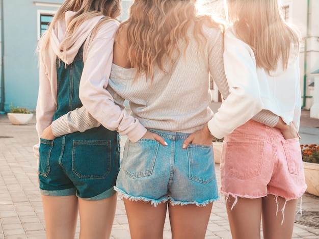 Widok z tyłu trzech młodych przyjaciółek hipster. dziewczyny ubrane w letnie ubrania casualowe. kobiety stojące na zewnątrz. wkładają ręce w szorty w tylnych kieszeniach. pozowanie o zachodzie słońca