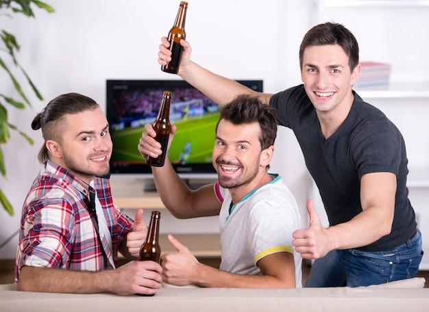 Widok z tyłu trzech podekscytowanych fanów piłki nożnej, siedząc na kanapie.