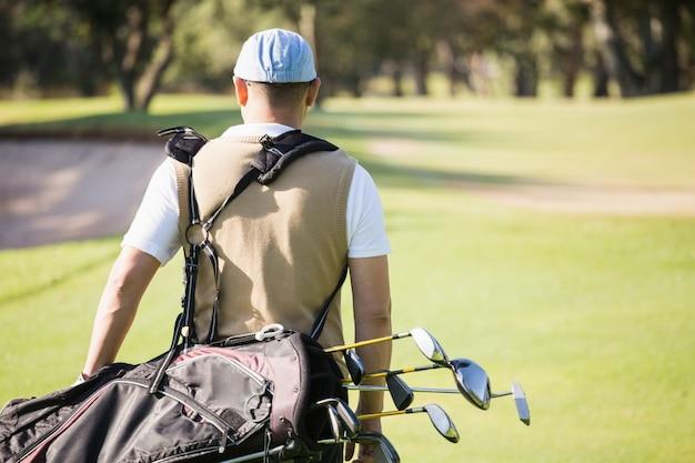 Widok z tyłu trzyma torbę golfową sportowca