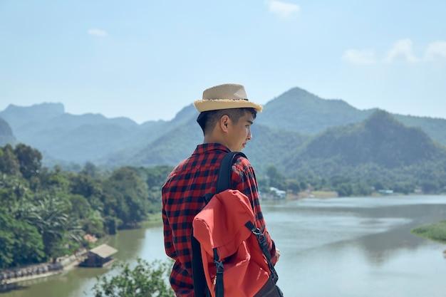 Widok z tyłu turystów płci męskiej, stojących z widokiem na góry i rzeki