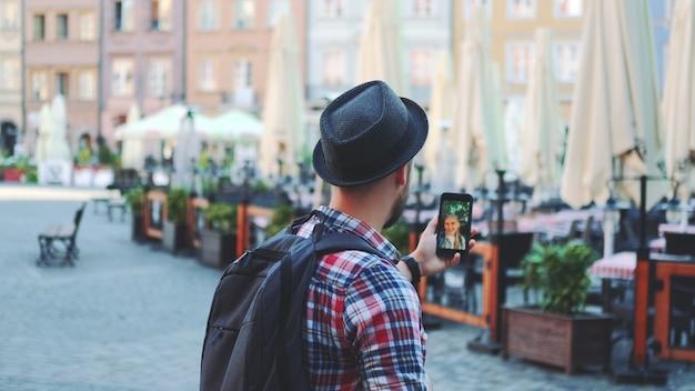 Widok z tyłu turysty nawiązywania połączenia wideo na smartfonie z turystką z innego miejsca